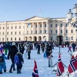 Das Osloer Schloss erstrahlt im Sonnenschein, während sich davor die Norweger im Schnee tummeln, der sorgsam ausgebreitet wurde.