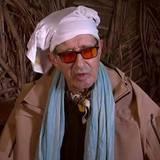 """Nein, hier sehen Sie keinen Sheikh aus einem Märchen aus Tausendundeiner Nacht, sondern Rolf Zacher im """"Dschungel-Telefon"""". Der Schauspieler scheint ein Faible für Schals und Tücher zu haben, anders können wir uns diese Halstuch-, Schal- und Turban-Kombi zumindest nicht erklären."""
