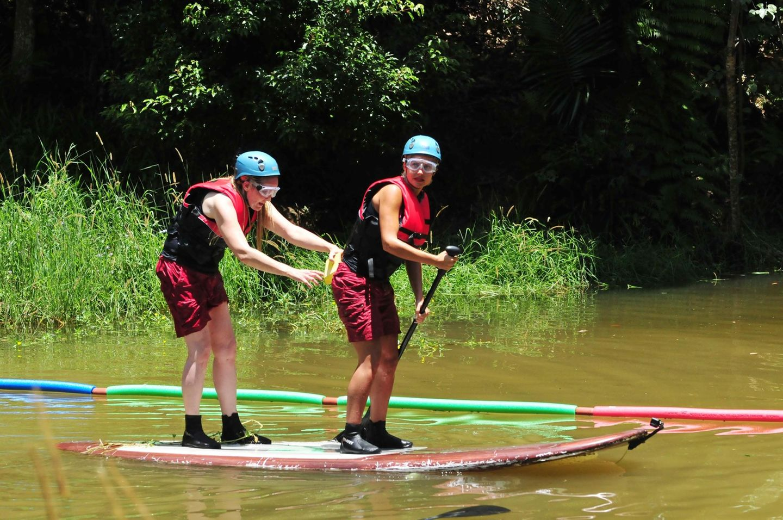 Die Beiden müssen gemeinsam auf einem Stand-Up-Paddling-Brett über einen See paddeln.