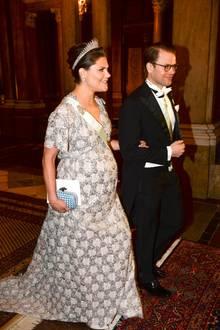 Silberglanz am Kleid und ein entspanntes Lächeln - Prinzessin Victoria und Prinz Daniel nehmen den Fotografentrubel, der ihr Eintreffen beim Galadinner begleitet, ganz professionell. Die Kronprinzessin, deren zweites Kind schon in wenigen Wochen zur Welt kommen wird, entschied sich für ein Abendkleid, dass sie schon während der Schwangerschaft mit Prinzessin Estelle getragen hat. Allerdings werden die Hofschneider wohl ein paar Änderungen vorgenommen haben, denn damals passte es der Prinzessin im Dezember perfekt, und das, obwohl Klein-Estelle auch ein Februarkind war.