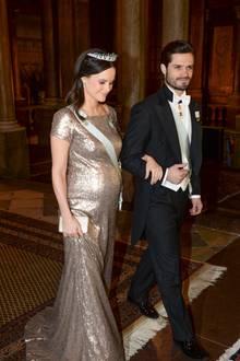 Goldig und wunderschön: Prinzessin Sofia am Arm ihres Mannes, Prinz Carl Philip, bei der Ankunft zum Galadinner im Schloss. Sie trägt ein Pailettenkleid, das aus ihrem Siebenmonatsbauch kein Geheimnis macht. Im gesteckten, halb offenen Haar trägt sie - wie so oft bei diesen Auftritten - ihre Hochzeitstiara.
