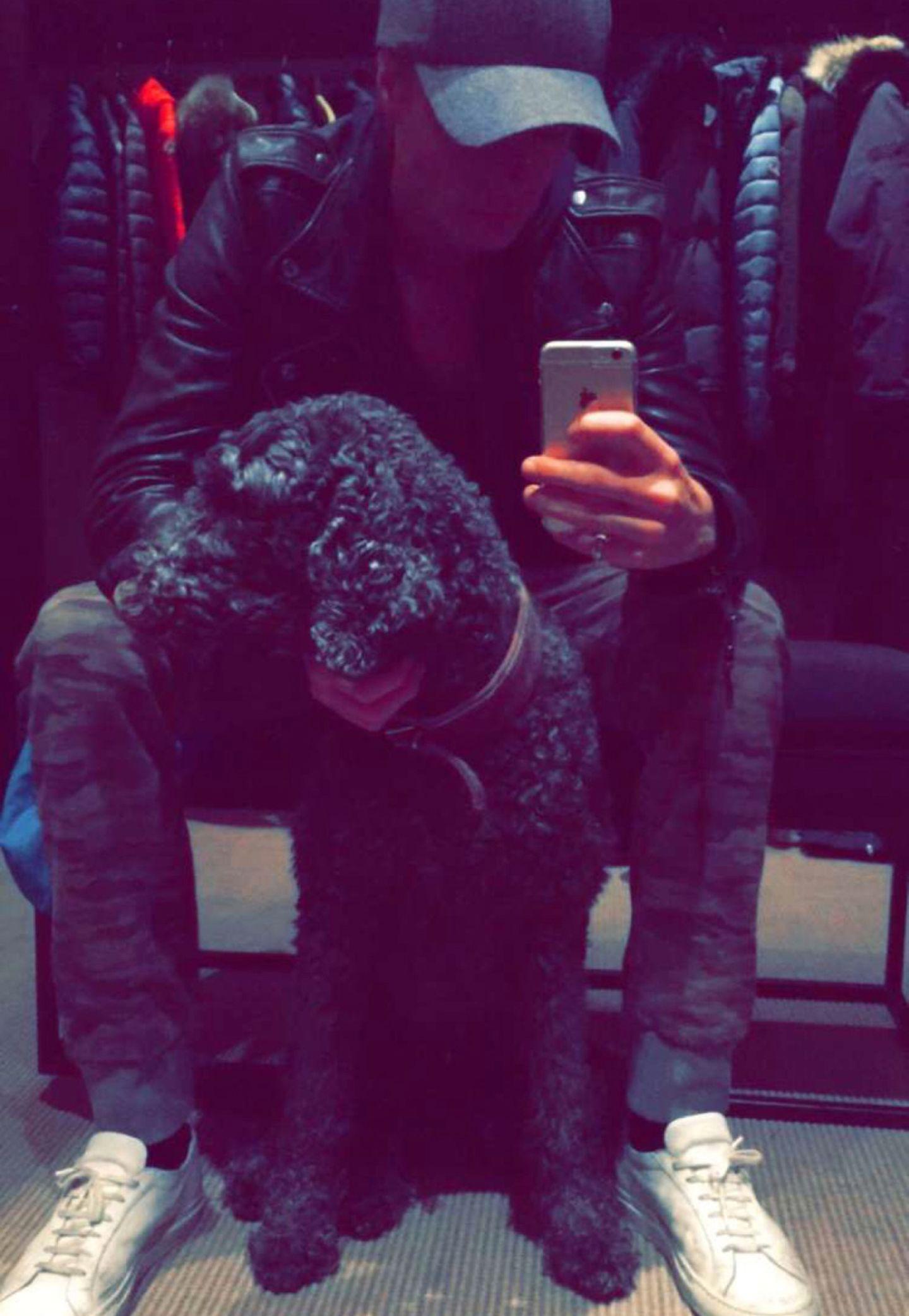 Sneaker-Fan Marius nutzt eine kurze Verschnaufpause beim Shopping für ein Selfie mit seinem Hund.