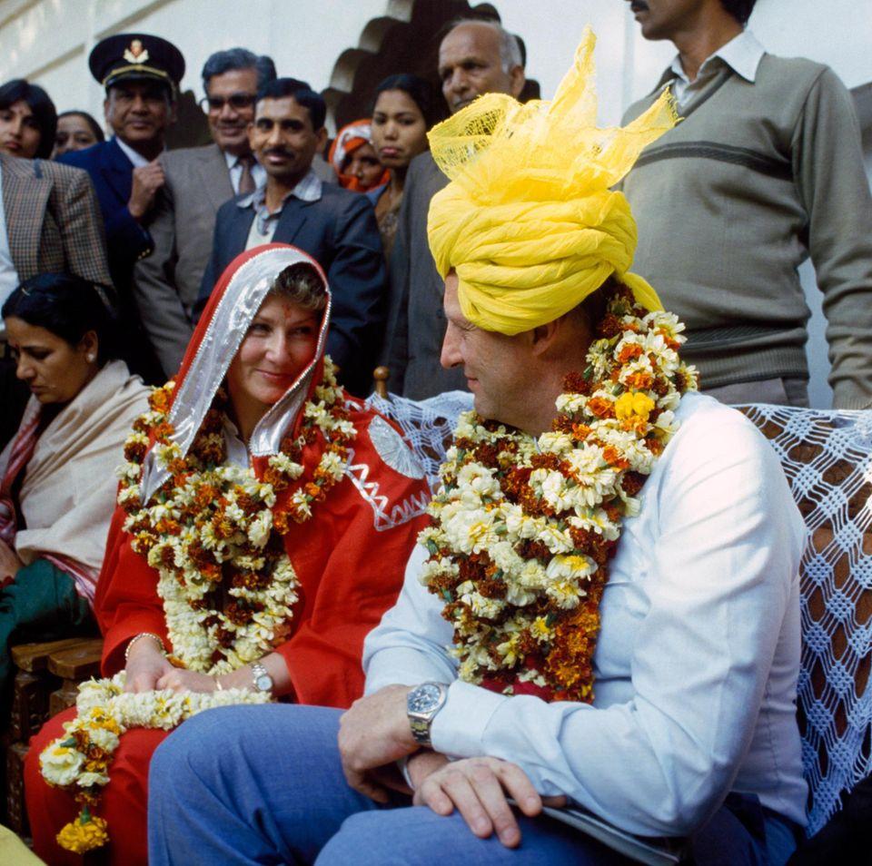 Als Königin Sonja und König Harald von Norwegen in 1986 Indien besuchen, lassen sie sich von den Einheimischen ganz landestypisch in Blumenkränze, Sari und Turban hüllen.