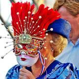 Federn, Perlen, knallige Farben: Bei einem Musikfestival in der Karibik versteckt sich Prinzessin Beatrix hinter einer landestypischen Maske.