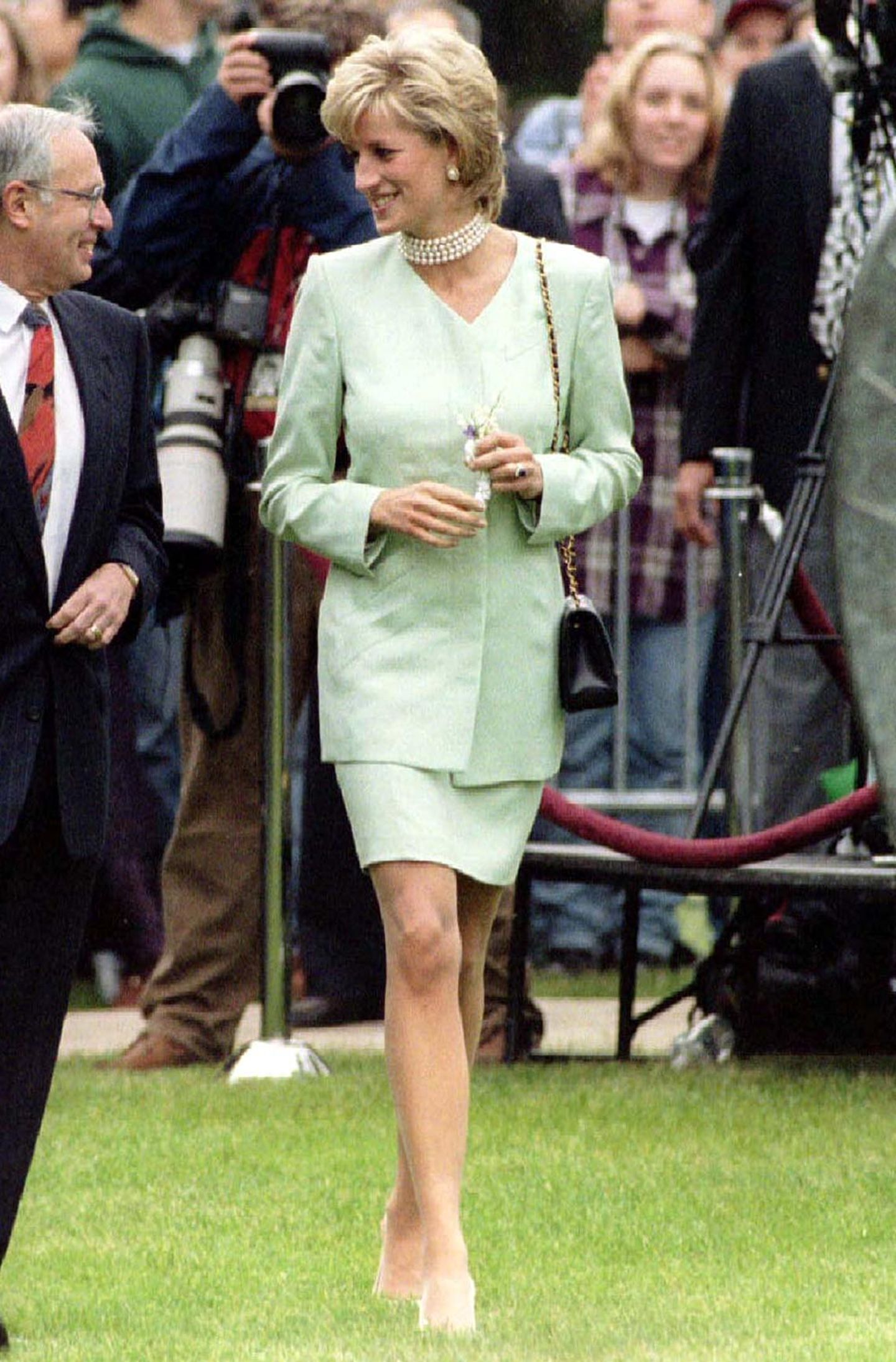 Für den Besuch einer Gartenschau kombiniert Diana ein frisches, lindgrünes Ensemble mit enganliegender Perlenkette.