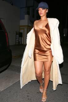 Hängerchen in Satain-Optik, weißer XL-Pelz und silberne Riemchensandalen: Popstar Rihanna im kompletten Millenium-Gedächtnislook, gekrönt mit einer blauen Basecap.