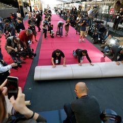 Es braucht eine Menge Arbeiter um den über 100 Meter langen und gut zehn Meter breiten Roten Teppich auszurollen.