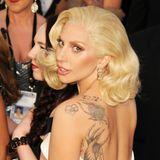 Die Tattoos von Lady Gaga kommen in ihrem weißen Jumpsuit von Brandon Maxwell dank eines in der Mitte zulaufenden Rückenausschnittes besonders gut zur Geltung.
