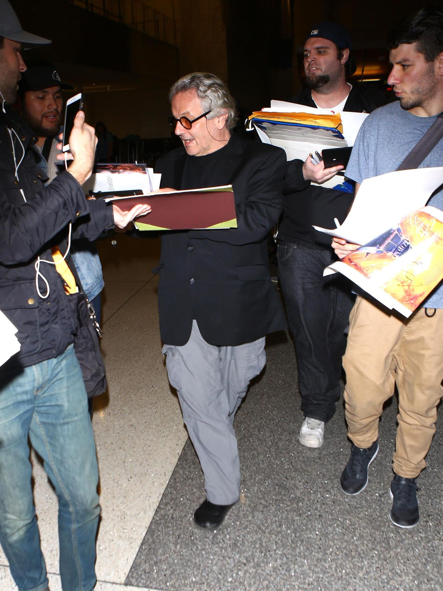 """""""Mad Max: Fury Road""""-Director George Miller wird am Flughafen von Fans um ein Autogramm gebeten."""