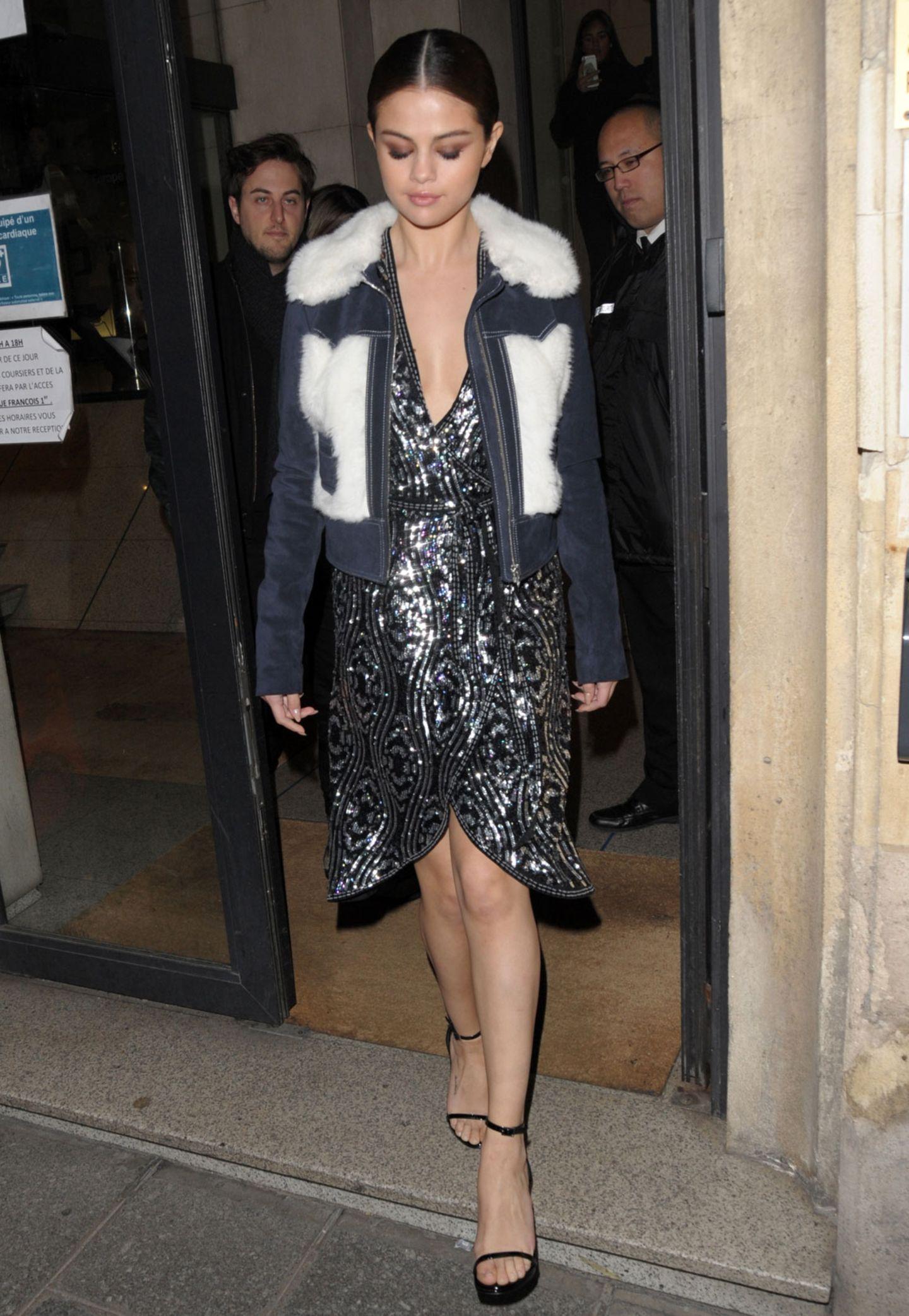 Trés chic - natürlich tritt der amerikanische Popstar in Paris mit einem Glitzerdress mit verführerischem Schlitz auf und streckt die Beine mit High Heels. Das Jäckchen hat sie einfach darüber geworfen.