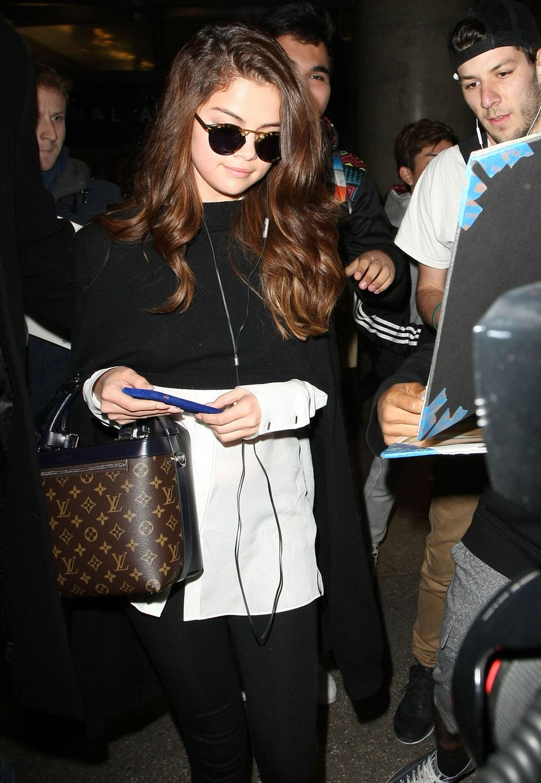 In Los Angeles am Flughafen trägt Selena Gomez ihren lässigen, aber stylischen Reise-Look mit Sneakers, Leggins, Glamourlocken: Accessoires wie die Sonnenbrille und ihre coole It-Bag von Louis Vuitton machen das Outfit zum Hingucker.