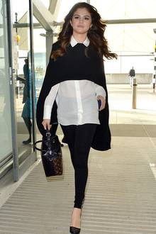 Schwarz-Weiß und klassisch - so wird der Flughafen Heathrow zum Laufsteg für Sängerin Selena Gomez, sehr schick aufgewertet mit Handtasche und spitzen Pumps.