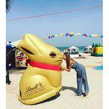 Cathy Hummels küsst am Strand einen überdimensionalen Lindt-Goldhasen.