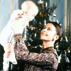 Das erste Weihnachtsfest: Stolz hält Königin Silvia ihren Sohn. Zu diesem Zeitpunkt ist Prinz Carl Philip als Zweitgeborener der Thronfolger, da eine weibliche Thronfolge mit Victoria als Erstgeborene noch nicht möglich war. Das Gesetz von 1810 wurde 1980 geändert.