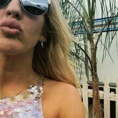 Ellie Goulding gewährt uns aus dem mit Wohnwagen ausgestatteten Künstler-Bereich eine Nahaufnahme auf ihr glamouröses Pailletten-Top und die schicke Fendi-Sonnenbrille.