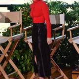 Emma Roberts ist mit leuchtend roter, knallenger Bluse, schwarzem Bleistift-Rock und hohen Stilettos ein richtig eleganter Blickfang.
