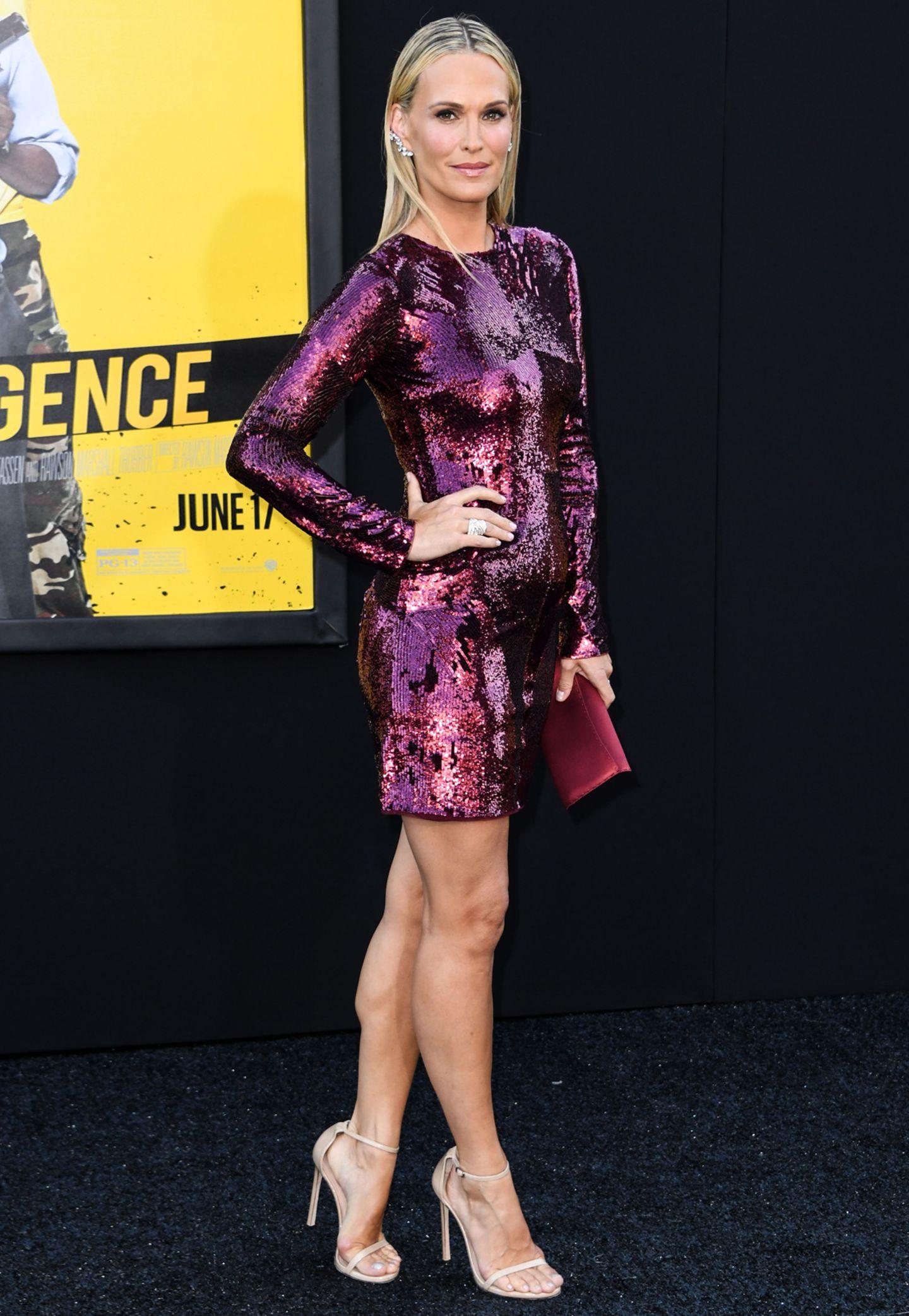Molly Sims akzentuiert ihr lilafarbenes Paillettenkleid gekonnt mit nudefarbenen Stilettos und Statementschmuck.