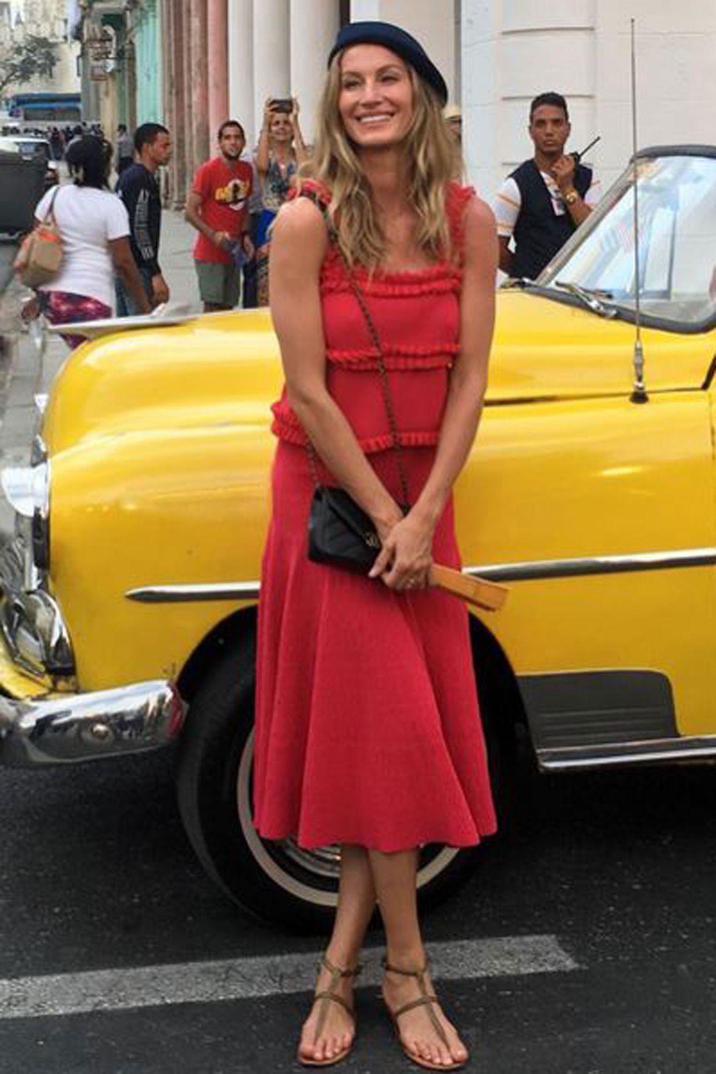 Supermodel Gisele Bündchen posiert vor einem knallgelben Oldtimer.