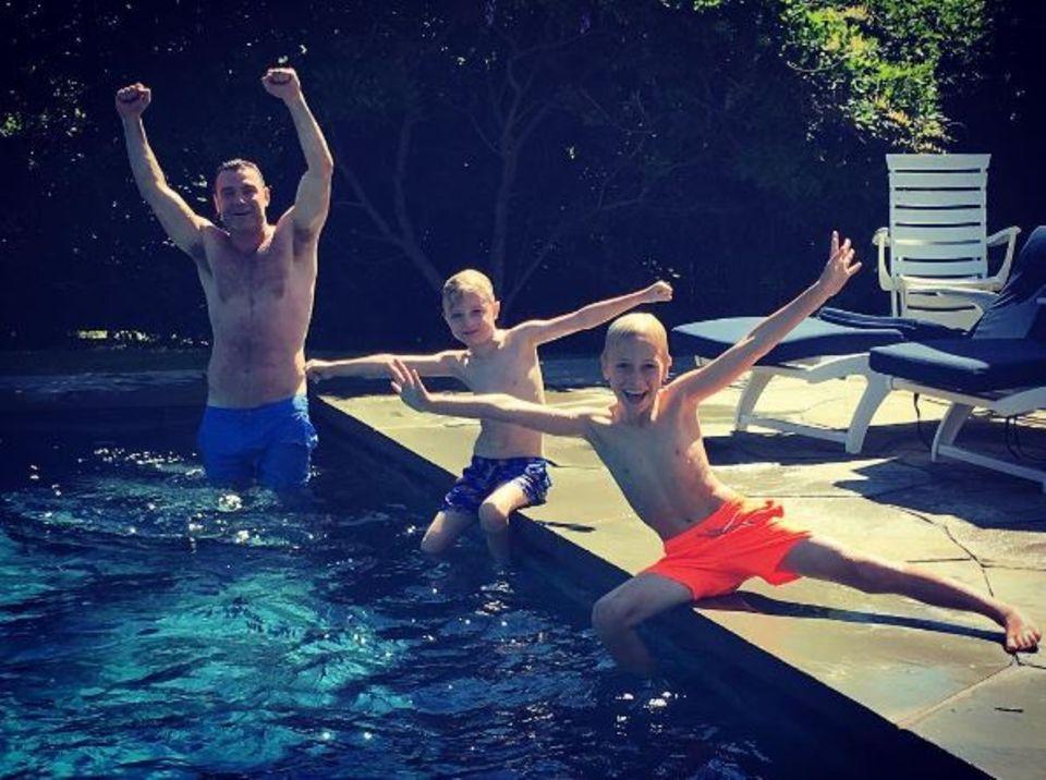 August 2016   Sommerzeit ist Badezeit: Liev Schreiber und seine beiden Söhne toben im Pool.