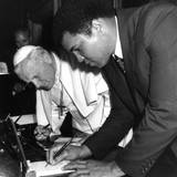 Juni 1982  Papst Johannes Paul und Muhammad Ali treffen sich im Vatikan. Am Ende unterzeichnen sie gegenseitig Autogramme füreinander.