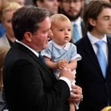 Prinz Nicolas ist zum ersten Mal bei einer königlichen Taufe dabei und scheint das Ganze ganz erstaunlich zu finden. Papa Chris beschäftigt den Kleinen mit einem Spielzeug.