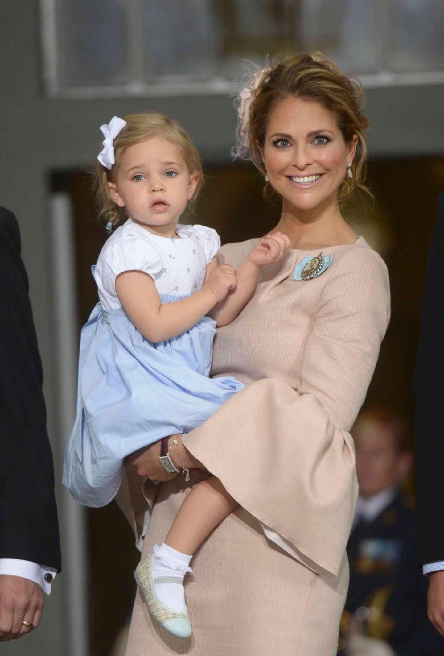 EIne strahlende Prinzessin Madeleine trägt ihre Tochter aus der Kirche.