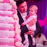 Gemeinsam mit ihrem Papa Lucas nimmt die kleine Sophia die achtstöckige Hochzeitstorte unter die Lupe.