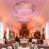 Festlich geschmückt ist die Kirche für die Hochzeitsgesellschaft bereit.