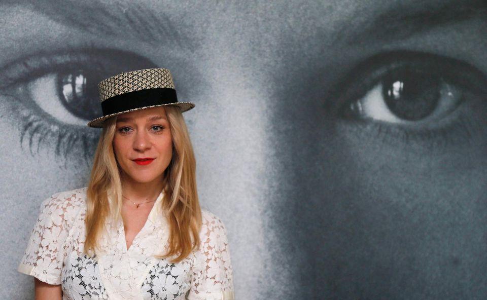 """Schlicht mit Hut posiert Chloë Sevigny vor einem Schwarzweiß-Plakat. Sie ist zu einer Veranstaltung von """"Kering Women in Motion"""" eingeladen."""