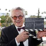 Regisseur George Miller strahlt, mit einer Filmklappe in der Hand, in die Kamera. Er leitet die diesjährige Jury in Cannes.
