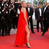In einem wunderschönen roten Kleid, aber etwas schlecht gelaunt, posiert Supermodel Kate Moss für die anwesende Presse.
