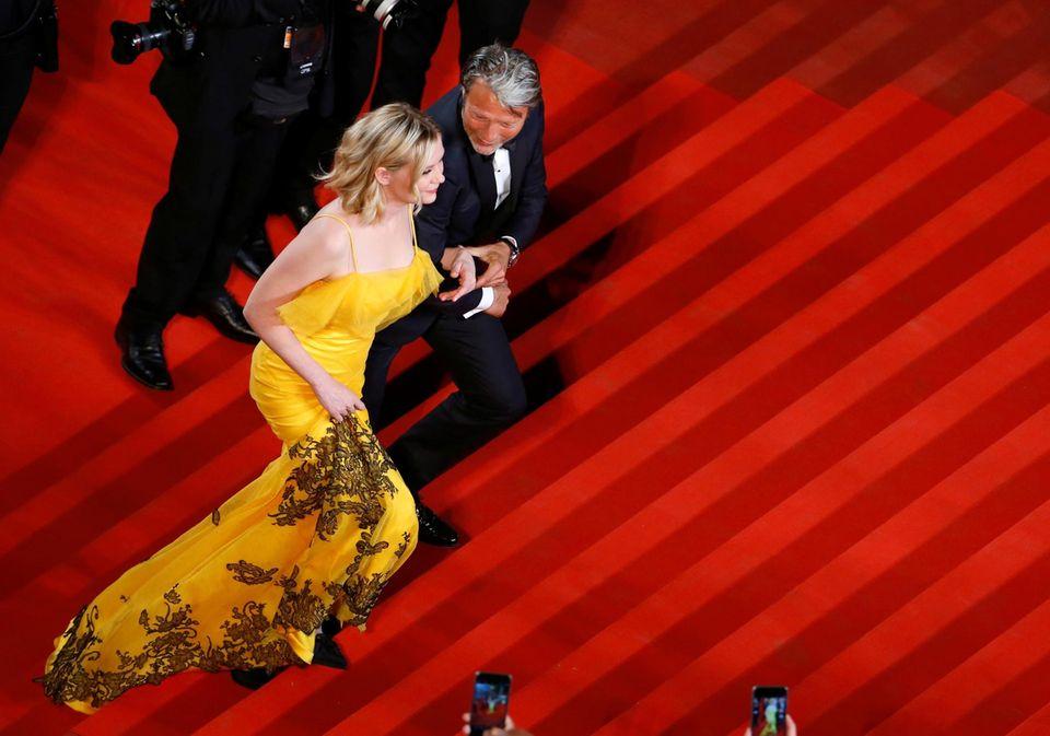 """Kirsten Dunst wird von Mads Mikkelsen bei der """"The Neon Demon""""-Premiere die Treppe hinaufbegleitet."""