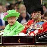 """Was für eine Farbe! Queen Elizabeth II. begeht die Feierlichkeiten zu Ehren ihres 90. Geburtstages in Neongrün. Gatte Prinz Philip wählt die klassische Uniform inklusive Bärenfellmütze der britischen """"Grenadier Guards"""", deren Ehrenoberst er ist."""