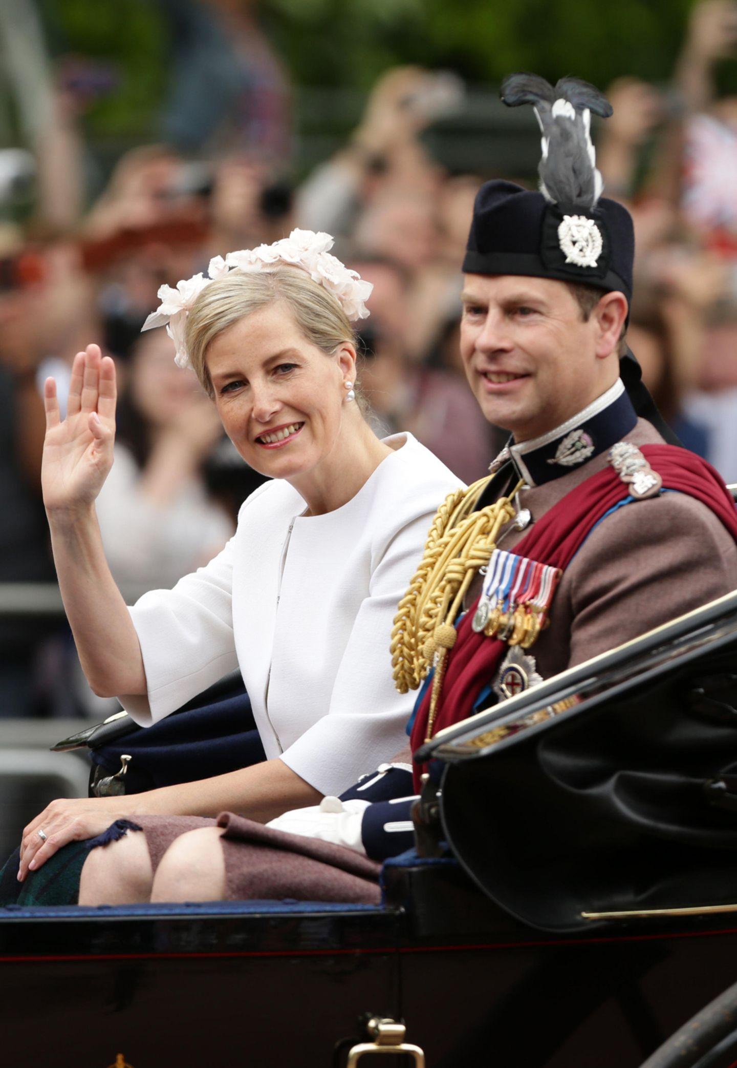 Prinz Edward (mit fragwürdigem Federschmuck) und seine schöne Frau, Gräfin Sophie von Wessex, sind in gewohnt schlichten Outfits bei der Feier dabei.