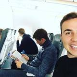 Mario Götze strahlt iim Flieger in die Kamera und fotografiert nicht nur sich, sondern auch Teamkollegen Thomas Müller, der vertieft eine Zeitschrift liest.