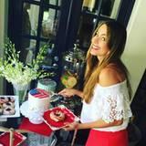 """Sofia Vergara bedient sich am Kuchenbuffet. Die Torten und Donuts sind natürlich dem Motto """"Stars and Stripes"""" angepasst."""