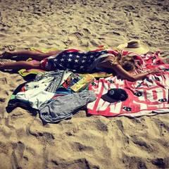 In eine USA-Flagge gehüllt, macht es sich Heidi Klum am Strand gemütlich.