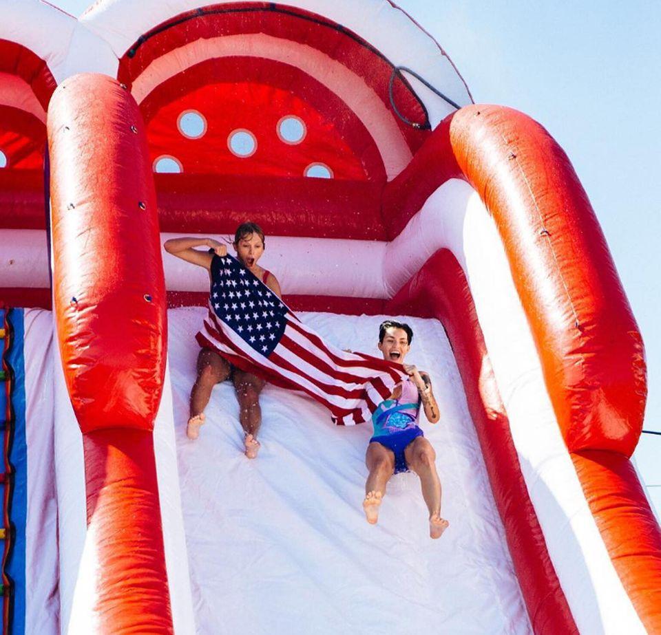 So feiern Stars den Unabhängigkeitstag: Taylor Swift und Ruby Rose halten beim Rutschen eine Flagge.