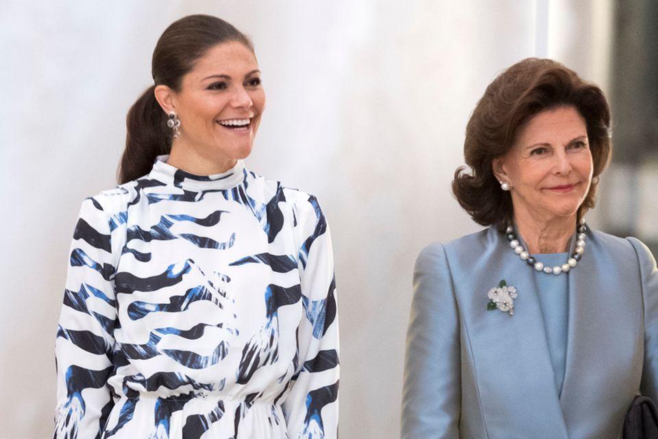 """Bei der Eröffnung der Ausstellung über königliche Brautkleider in Stockholm trug Prinzessin Victoria, hier mit Mutter Königin Silvia, ein gemustertes Kleid von """"Whyred"""". In diesem Outfit zeigte sich die schwedische Thronfolgerin bereits vor weniger als vier Wochen im Rahmen eines öffentlichen Auftittes in New York."""