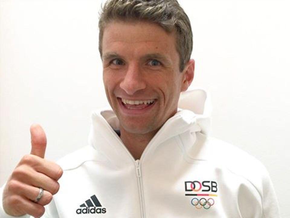 Für eine Reise nach Rio hat der Fußballstar Thomas Müller leider keine Zeit: Er feuert die deutschen Olympia-Teilnehmer fleißig vor dem Fernseher an.