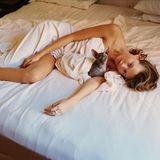 Ein Bein draußen und nur mit einem dünnen Laken bedeckt verbringt Behati Prinsloo die Zeit im Bett mit ihrer Katze.
