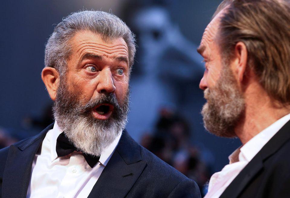 Mel Gibson belustigt seinen Schauspielkollegen Hugo Weaving auf dem roten Teppich mit lustigen Grimassen.