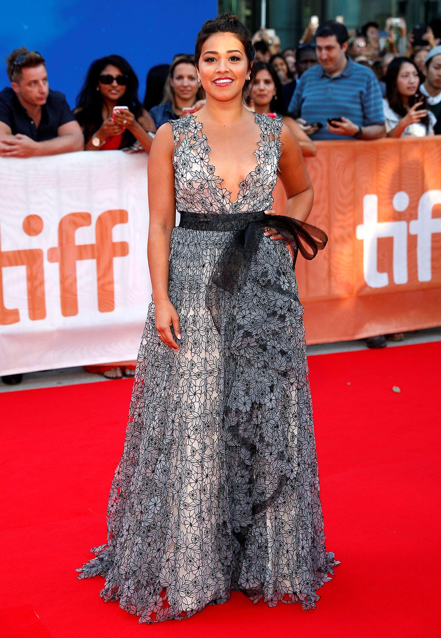 """""""Jane the Virgin""""-Schauspielerin Gina Rodriguez ist in ihrem bodenlangen Blütenkleid noch mit einer Schleife verpackt."""