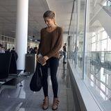 """Boarding Time am Münchner Flughafen: Cathy reist in einer bequemen Leggings von Victoria's Secret, kombiniert dazu einen Pullover von Marc Cain, """"Susanna""""-Boots von Chloé und eine schwarze Tasche von Bottega Veneta."""