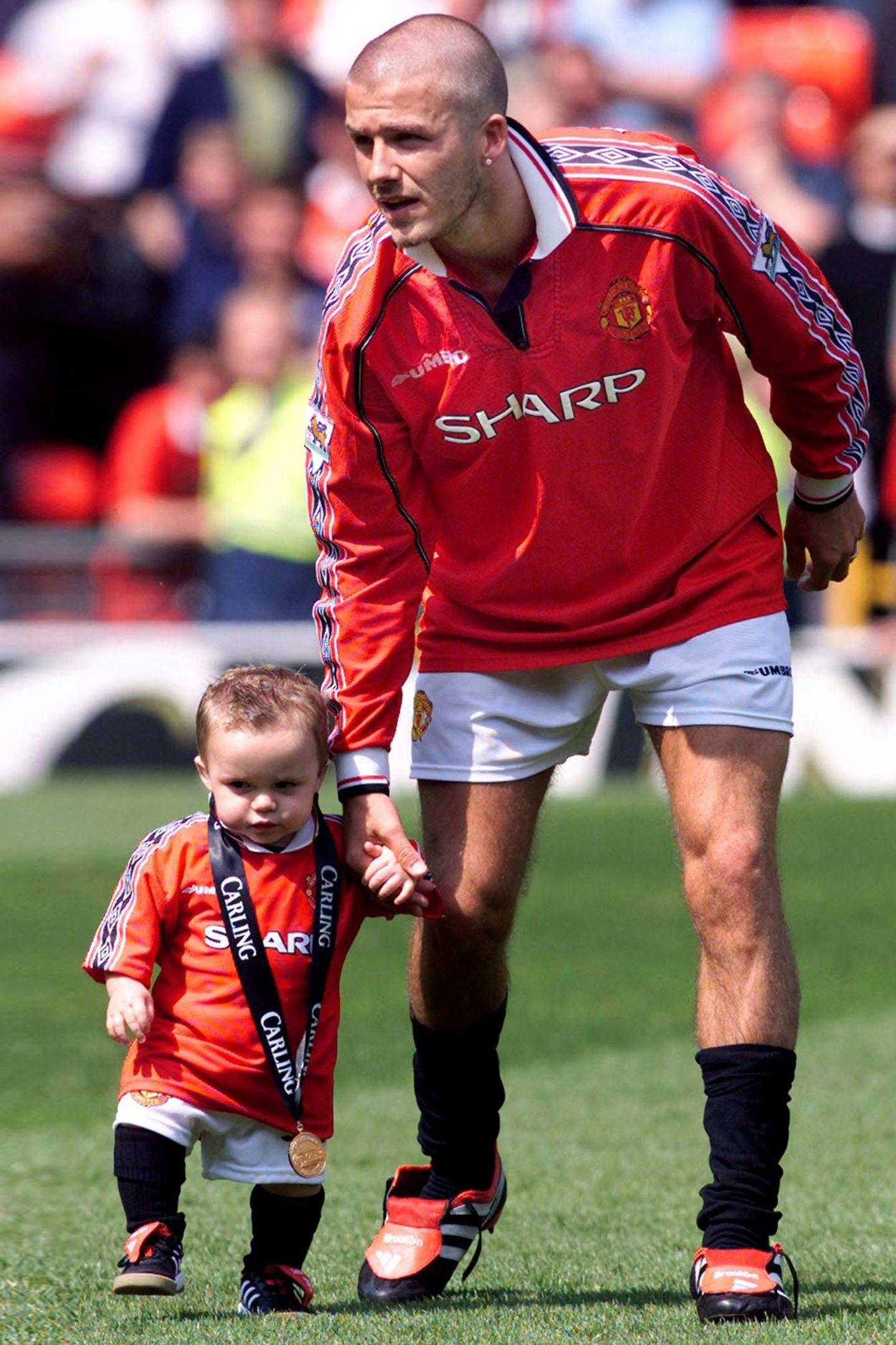 """2000 feiert David Beckham den Sieg der """"Premier League"""" mit seinem Verein Manchester United. Söhnchen Brooklyn ist damals gerade einmal ein Jahr alt war."""