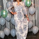 Karen Webb trägt ein bodenlanges mit Ornamenten verziertes Kleid.