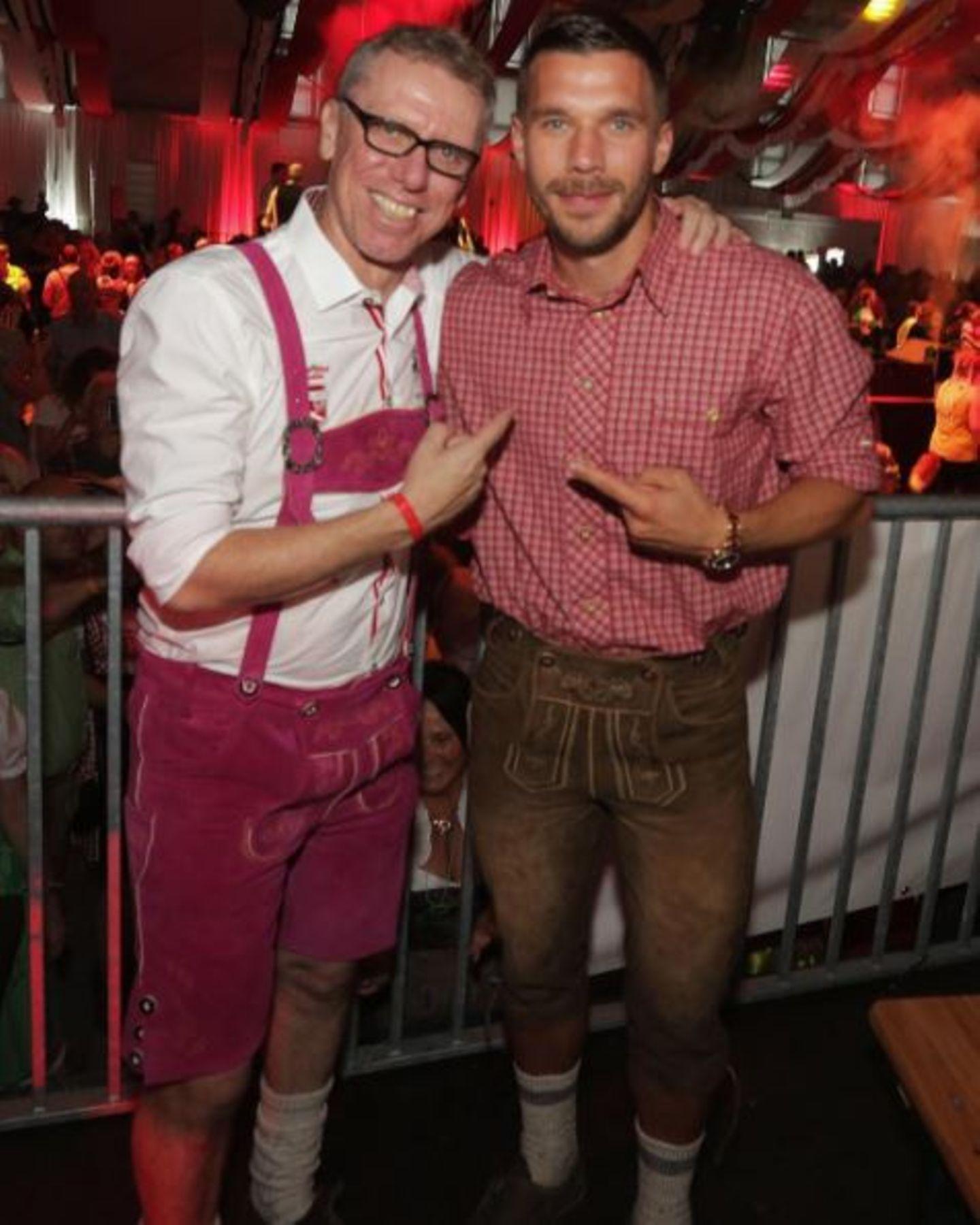 Lukas Podolski posiert mit dem FC-Trainer Peter Stöger, der ganz fesch eine pinke Lederhose trägt.
