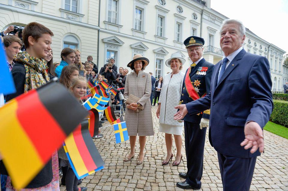Tag 1  Warmer Empfang: Bundespräsident Joachim Gauck, Daniela Schadt und jede Menge Kinder heißen das schwedische Königspaar willkommen.