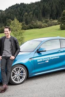Moderator Alexander Mazza posiert vor einem BMW M.