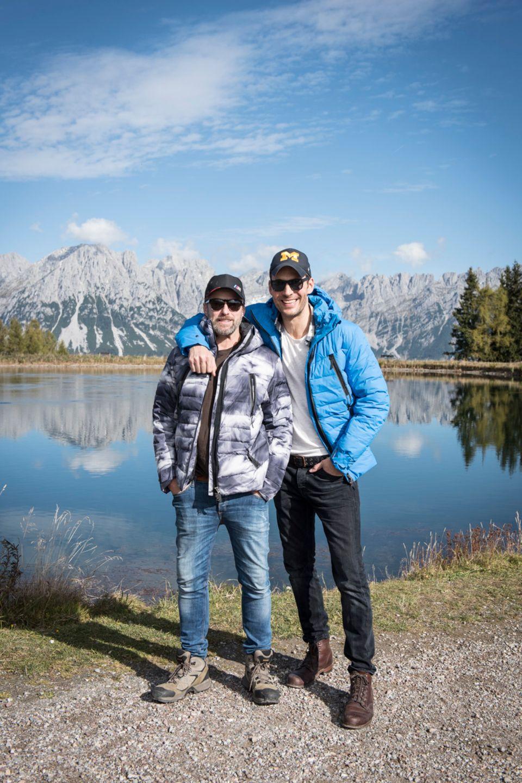 Schauspieler Bruno Eyron und Moderator Alexander Mazza posieren vor der traumhaften Kulisse in Tirol bei der Wolfskin Tech Lab Outdoor Experience.